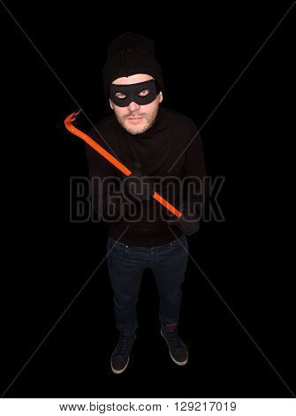 Masked burglar is going to try to break into someone's home. Handsome man in black using special equipment crowbar. Isolated on black.