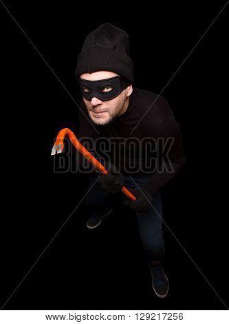 Masked thief in balaclava is going to steal or rob house at night. Handsome man with crowbar over black background. Isolated on black.