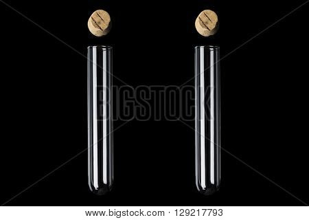 Two glass transparent test tubes with cork above on black background