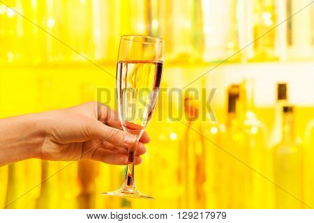 Hand with full glass of champagne on yellow background