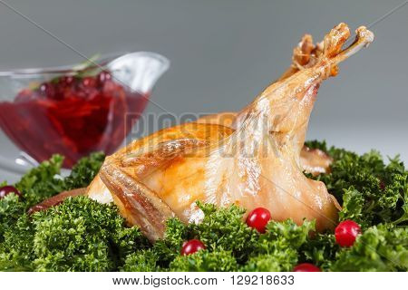 Carcasses of quail roasted with sweet and sour cranberry sauce and parsley