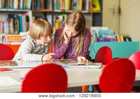 Two adorable kids, little girl and her brothe reading book in a library
