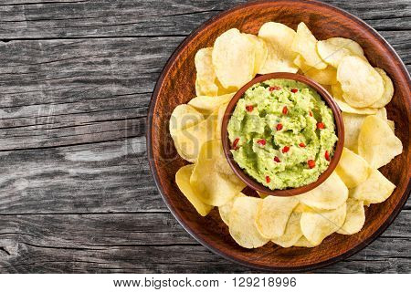 bowl of guacamole dip and potato chips on a clay brown dish on a wooden background view from above