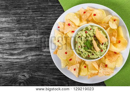 bowl of guacamole dip and potato chips on a clay brown dish on a wooden background close-up