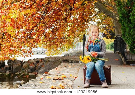 Autumn portrait of adorable little blond girl of 8 years old, wearing warm pullover, denim overalls and beige shoes, sitting on the old vintage suitcase, holding red apple and bouquet of yellow sunflowers