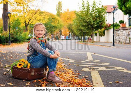 Autumn portrait of adorable little blond girl of 8 years old, wearing warm pullover, denim overalls and beige shoes, sitting on the old vintage suitcase