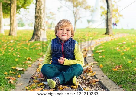 Autumn portrait of a cute little boy of 4 years old, playing with yellow leaves in the park, wearing blue jacket and green trousers