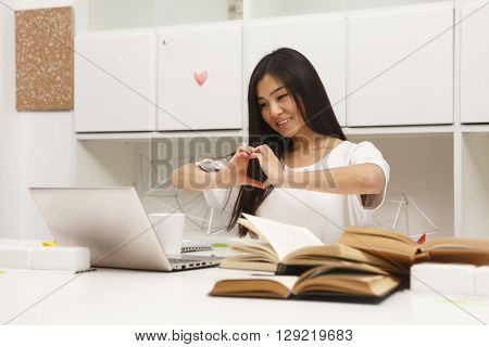 Asian student communicating with foreign friends and showing heart to them. Beautiful woman sitting in library and studying.