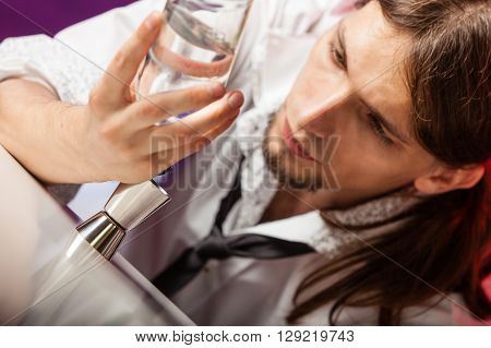 Drink alcohol liquor drink relax concept. Closeup of barman at work. Male bartender looks at glass and bottle.