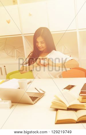 Top view of Asian student lady communicating via Skype with her foreign friends while sitting in library. Brunette woman sitting in front of laptop computer. Toned image.