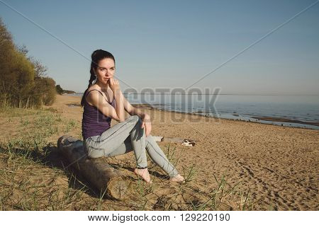 Pensive or thoughtful caucasian young woman in casual blue jeans, barefoot sitting on a wooden log on the coast river. Brunette serious female walking outdoors in summer morning on sea background.