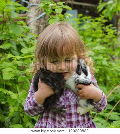 little girl playing with black and spotted rabbits