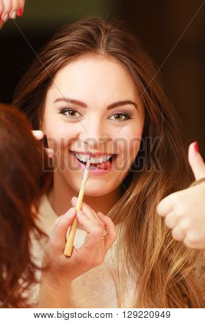 Beautician making makeup for smiling girl. Woman take care about look in salon. Giving thumbs up.