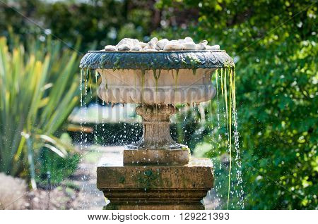 Close up of cool refreshing water splashing from a garden fountain