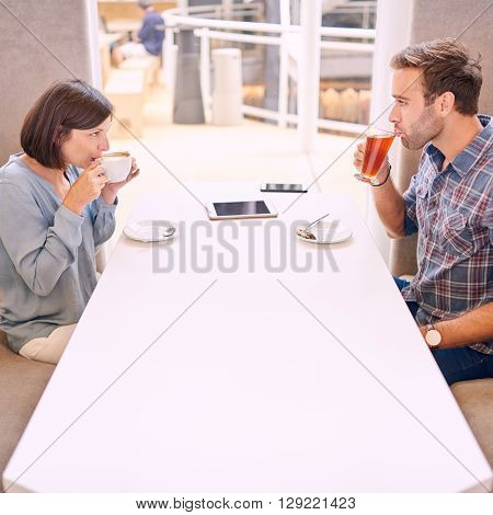 Couple looking at each other as they take their first sip on their first date after meeting online through a dating agency. There is a phone and tablet on the table.