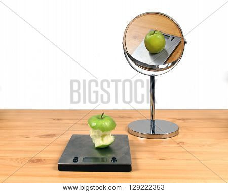 Concept about body image distortion with eaten apple and fat apple in the mirror