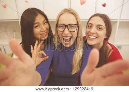 Happy students making selfies on mobile or smart phone and happy smiling and laughing in library. Beautiful ladies studying. Toned image.