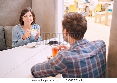 Woman looks at someone out of the frame with a polite smile, while having a drink with her male partner whom is busy talking to her as she fails to show interest.