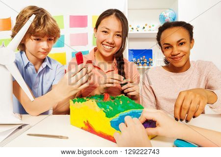 Three teenage kids creating topographical relief with modeling clay at the classroom