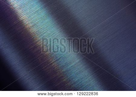 Tough brushed metal with slight rainbow like reflection. Shallow depth of field.