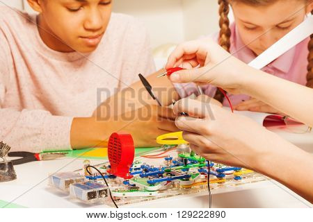 Young students measuring electrical voltage of electric chain with potential probes