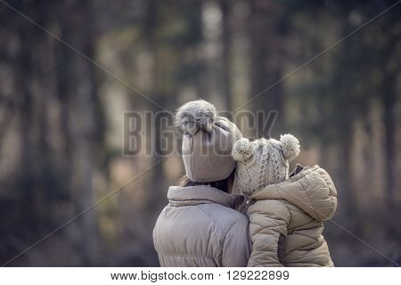 View from behind of a mother holding her child both wearing winter jackets and warm hats with blurred trees of the forest in background. With retro filter effect.