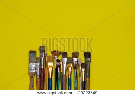 Row of paintbrushes on a neon yellow surface