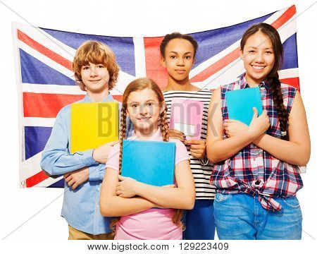 Four happy multiethnic teenage students standing against British flag, holding textbooks, isolated on white