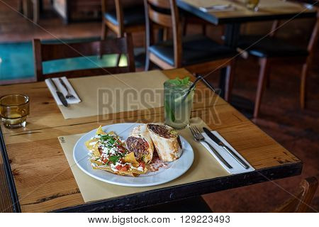 mexican chili burrito with corn chips and lemonade