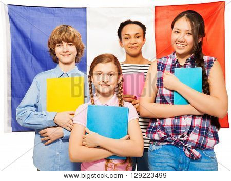 Four happy multiethnic teenage students with textbooks standing against French Flag, isolated on white