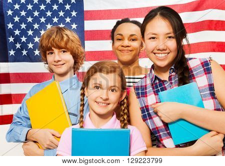 Close-up picture of four smiling multiethnic teenage students standing with textbooks against American flag