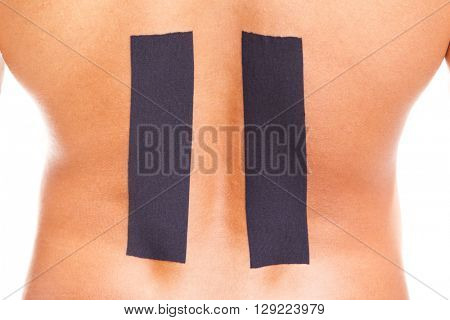 Muscular man with kinesiotaping on lower back, isolated on white background