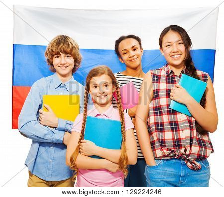 Four happy multiethnic teenage students standing against Russian flag, holding textbooks, isolated on white
