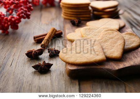Heart shaped biscuits on cutting board with ash berry and cinnamon on wooden background