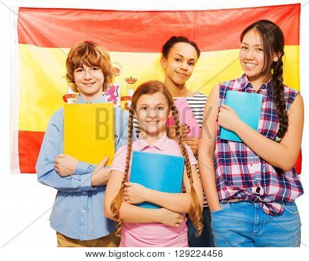 Four happy multiethnic teenage students standing against Spanish flag, holding textbooks, isolated on white