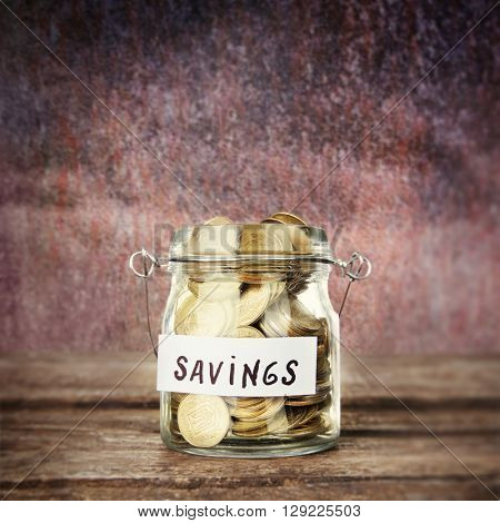 Jar for savings full of coins on blur background