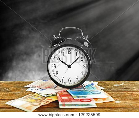 Alarm clock and money on wooden table, grey background
