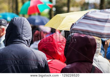 crowds of people with umbrellas and rainjackets on the move while it is raining