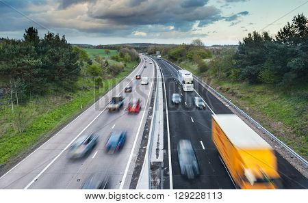 Cars in Motion on Dual Lane Motorway Among Green Spring Fields