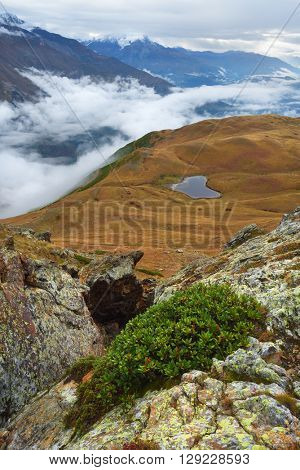 Caucasus, Georgia, Zemo Svaneti. Mountain landscape in the autumn. A small lake on the slopes
