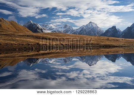 Beautiful mountain lake. Reflection of clouds in water. Lake Koruldi. Caucasus, Georgia, Zemo Svaneti