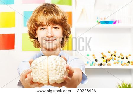 Young 13 years old boy holding cerebrum model at the biology room