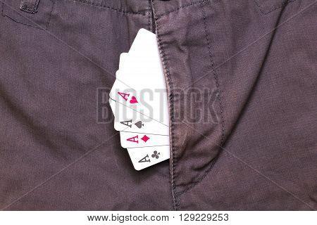 four ace cards inside purple jeans fly closeup