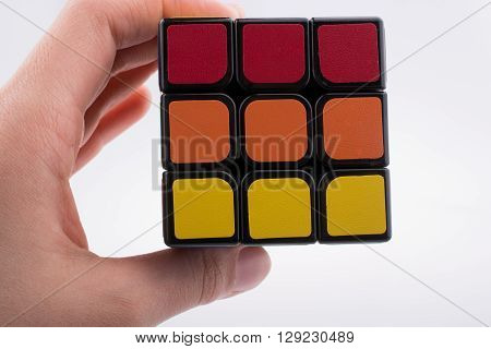 hand holding Rubik's cube on white background