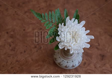 White flower with green leaf in bouquet put in ceramic vase on brown wooden table/White flower in vase on wooden table top view