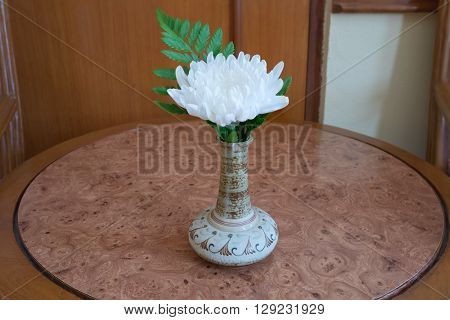 White flower with green leaf in bouquet put in ceramic vase on brown wooden table/White flower in vase on wooden table