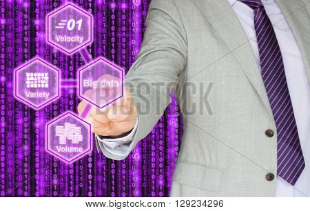 Hand pressing a big data button showing the three components of big data which are velocityvolume and variety on purple