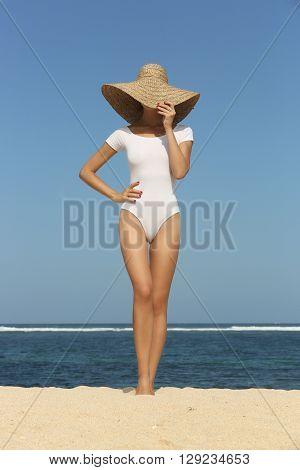Girl posing n the beach wearing big straw hat