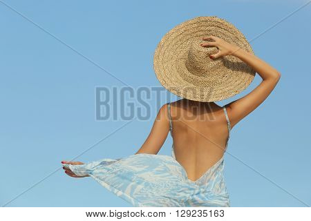 Girl with the big straw hat - back view