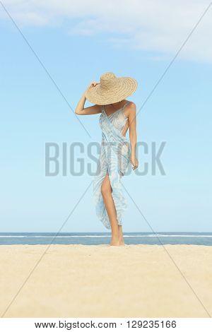 Girl posing on the beach wearing big straw hat